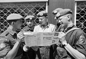 "Canadian and Swedish soldiers serving with UNFICYP read ""The Blue Beret"" a UNFICYP newspaper, 18 April 1964 [UN Archives 52051]"